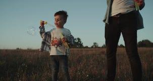 Doornemende zoete jongen, het gebied bij zonsondergang, charismatische drie jaar jongens stock video