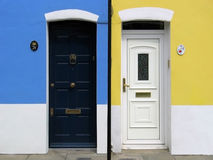 Doors. These are two neighboring entrances on colorful walls. On the small tables you can read the address numbers: 24 and 26. This is a real shot not a montage Royalty Free Stock Photo