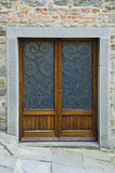 Doors of Cortona, Italy. A beautiful set of wooden doors, complete with wrought iron insets is the entrance into a building within the walls of Cortona, Italy Royalty Free Stock Photography