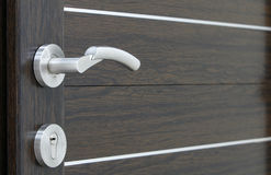 Doors detail. A silver handle with pvc brown door Royalty Free Stock Photo