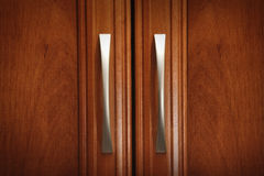 Doors and handles. Two cabinet handles on a wooden door Stock Images