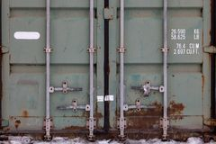 The doors of a large old container are painted in close-up in green with rust, with pipe-type locks and white lettering indicating
