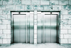 Doors of a lift. A pair lifts, blue-green tint Stock Images