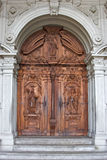 Doors of a temple. Wooden doors of a cathedral in Lucerne, decorated by woodcarving royalty free stock photos