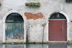 Doors by the water. Old characterful fading doors in a crumbling old venetian wall overlooking a canal royalty free stock photography