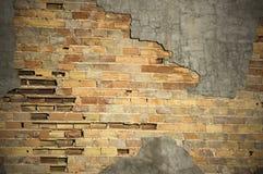 Doorstaan brickwall met gebarsten cementoppervlakte Stock Fotografie