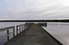 Doorstaan dok in een meer op een bewolkte dalingsdag Royalty-vrije Stock Foto