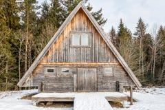 Doorstaan en oud die blokhuis door bomen en sneeuw wordt omringd stock foto's
