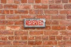 Doorstaan gereserveerd teken op bakstenen muur Stock Afbeelding