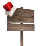 Doorstaan houten teken met de hoed van de Kerstman op wit Stock Afbeeldingen