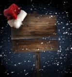 Doorstaan houten teken met de hoed van de Kerstman in sneeuw Royalty-vrije Stock Fotografie
