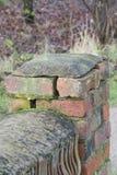 doorstane bakstenen muur die barsten tonen en mortier missen Stock Foto's