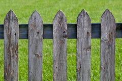 Doorstane grijze houten piketomheining Stock Foto