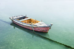 Doorstane houten die rijboot in groenachtig water wordt vastgelegd royalty-vrije stock foto's