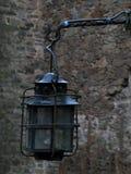 Doorstane Oude ijzer vervaardigde Lantaarn op een Steenmuur van oud Burg-Kasteel royalty-vrije stock afbeeldingen