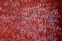 Doorstane rode verf waarop de abstracte verschillende cijfers door kinderen worden getrokken De slagen van de borstel Stock Fotografie
