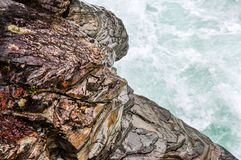 Doorstane Steen langs een snel Bewegende Rivier in Gletsjer Nationaal Park stock fotografie