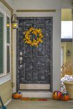 Doorway of home decorated with wreath and pumpkins royalty free stock photography