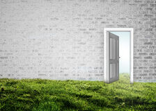 Doorway opening to blue sky in grey brick room Stock Photo