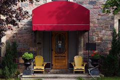 Doorway with red awning. Doorway with large red awning, yellow chairs on patio and multi-colored brick stock image