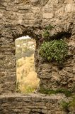 A doorway in the ruins of an ancient castle. Remains of the wall of the ancient castle with a doorway, overgrown with grass Royalty Free Stock Photos