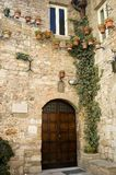 Doorway in stone building with flowers. Arched doorway in ancient stone building with potted flowers and plants Royalty Free Stock Image
