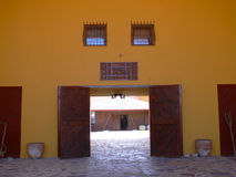 Doorway to cobbled courtyard. Double doors in a colorful painted wall open onto a cobbled courtyard containing workshops manufacturing carpets Stock Photography