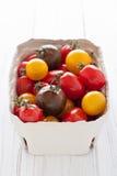 Doos met kleurrijke tomaten Stock Afbeeldingen