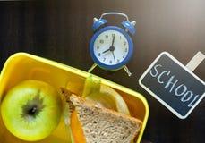 Doos van de school de gele lunch met sandwich, groene appel, potloden, klok op zwart bord Het gezonde eten op school stock foto's
