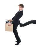Doos van het zakenman de dragende karton met been die hem schoppen stock foto's