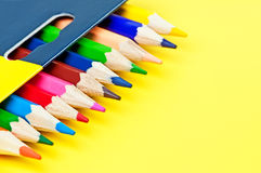 Doos van kleurpotloden op gele achtergrond. Stock Foto