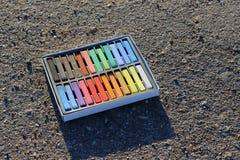 Doos van kleurrijke kleurpotloden, krijt op het asfalt Stock Afbeelding