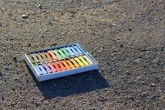 Doos van kleurrijke kleurpotloden, krijt op het asfalt stock foto's