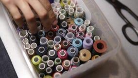 Doos van naaiende draadspoelen De mensenhand van de manierontwerper het graven in organisatorhoogtepunt van verschillende kleurri stock footage