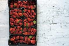 Doos van verse rijpe perfecte aardbeien op witte rustieke houten achtergrond Stock Afbeeldingen