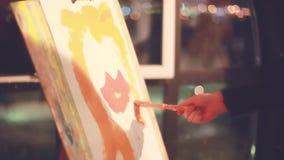 Doosschildersezel met canvas, olieverf, palet, en hulpmiddelen Hand van schilder op bokehachtergrond 1920x1080 stock videobeelden