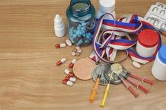 dopa sporten Missbruk av anabola steroider för sportar Anabola steroider som spills på en trätabell Arkivfoto