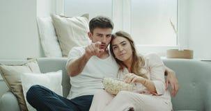Dopatrywania tv potomstwa dobierają się w ranku obsiadaniu na łasowaniu i kanapie duży talerz jest ubranym piżamy popkorn zdjęcie wideo