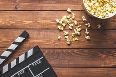 Dopatrywanie film z popkornem na drewnianego tła odgórnym widoku fotografia stock