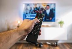 Dopatrywanie TV i używać dalekiego kontrolera zap kanały, pov sho Fotografia Stock
