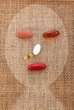 Dopez la pilule sur la forme en difficulté humaine de visage de toile de jute Photographie stock libre de droits