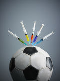 Doping. Five syringes threaded in soccer ball. Copy space Stock Photography