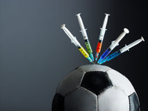 Doping. Five syringes threaded in soccer ball. Copy space Stock Photos