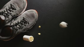 DOPING: Container with pills falls near a sneakers - slow motion, top view stock video footage