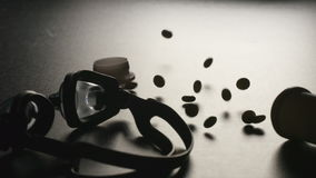 DOPING: Container with pills falls near a swimming glasses - slow motion, top view stock footage