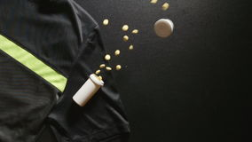 DOPING: Container with pills falls on a sport T-shirt - slow motion, top view stock video