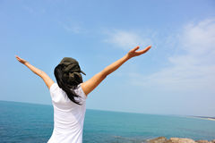Doping kobiety otwarte ręki przy nadmorski skałą Zdjęcia Stock
