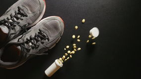 DOPING: Plastic bottle with pills falls near a sneakers - slow motion, top view stock video