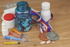 Doping in sport. Abuse of anabolic steroids for sports. Anabolic steroids spilled on a wooden table. Fraud in sports. Pharmaceutical industry. Detailed view of Royalty Free Stock Image
