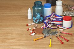 Doping in sport. Abuse of anabolic steroids for sports. Anabolic steroids spilled on a wooden table Stock Images
